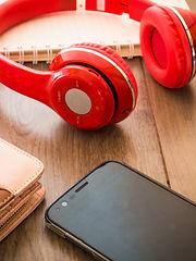 Red headphones next to mobile phone.jpg