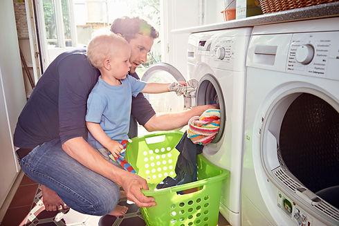 Father and young son putting washing in washing machine