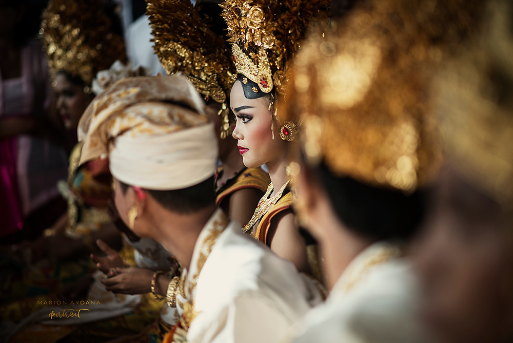 A young girl in focus in balinese costume sits waiting to join the teeth filing ritual in bali.