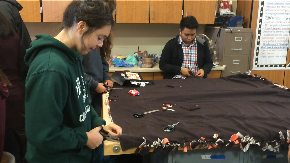 Seniors Clara Wolfe and Peter Valbuena work on their no sew blankets at Palo Alto High School
