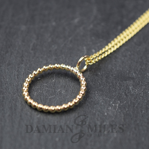 Circular Beaded pendant on a chain in 9ct yellow gold.