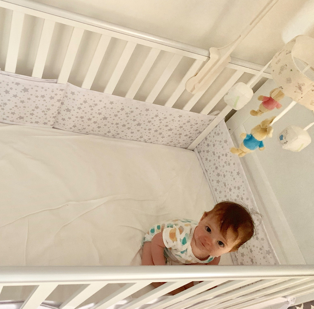 Baby Roxie inside her cot with the BreathableBaby cot liner