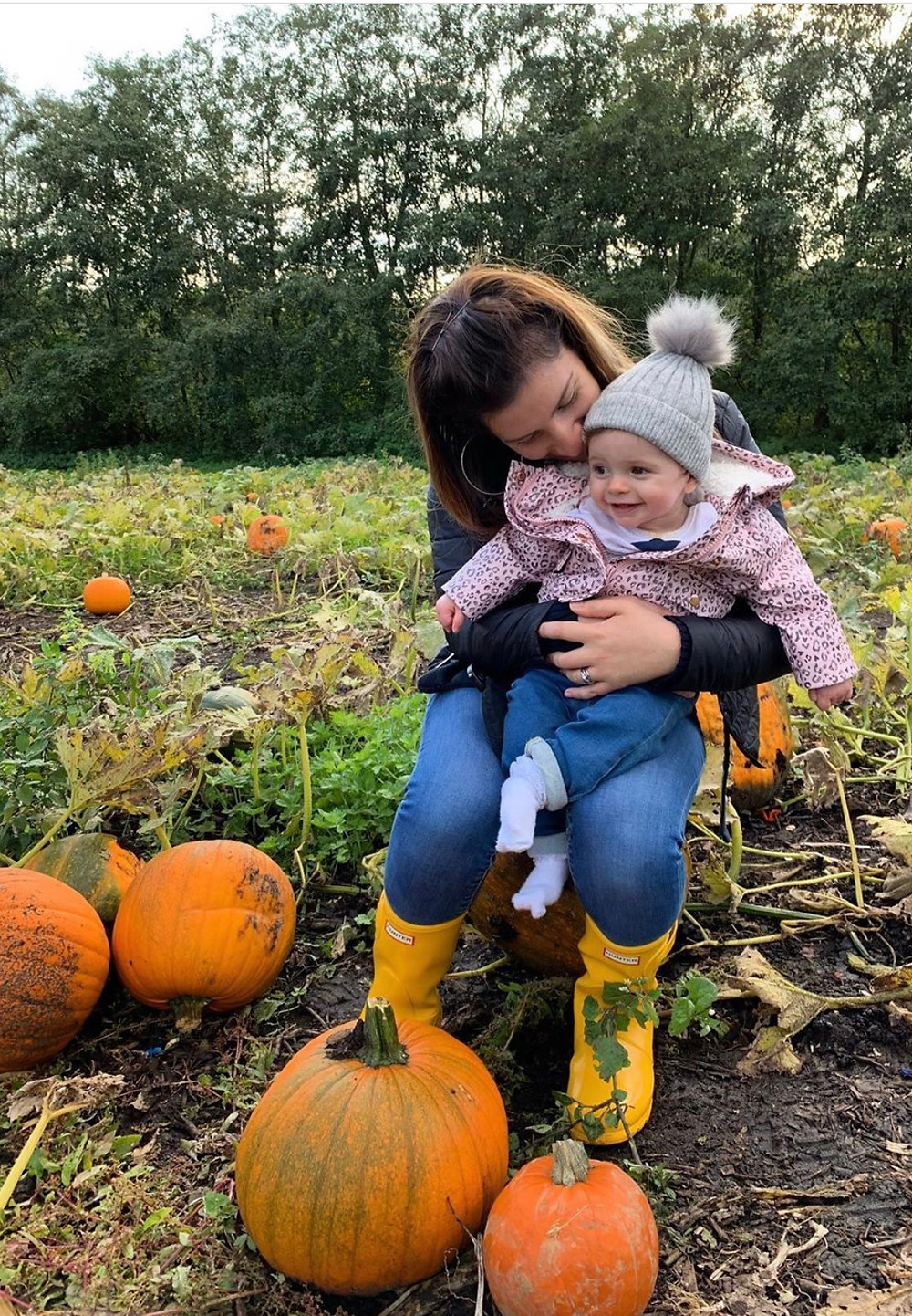 Mum with baby looking at pumpkins