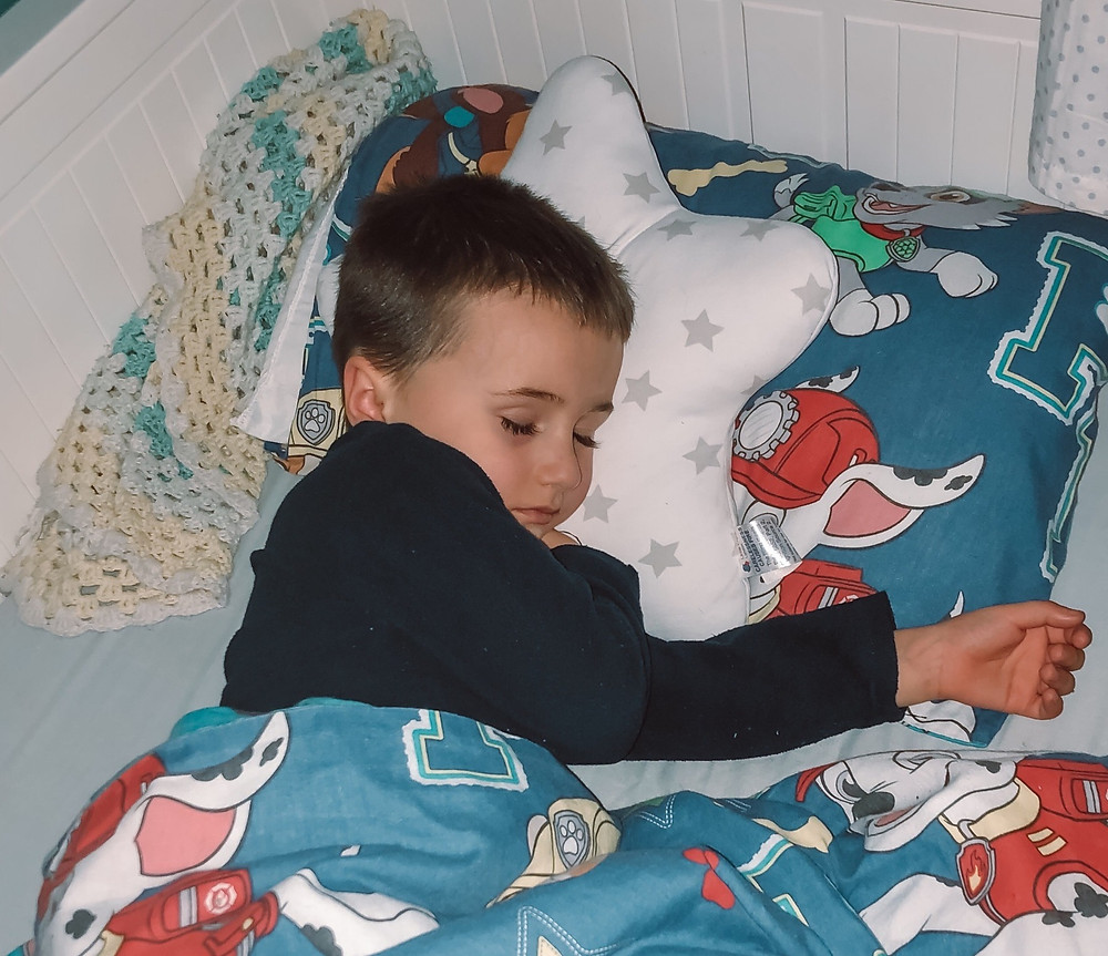 Little boy sleeping with a Little Chick London Star Toddler Pillow