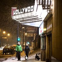 two people walking dogs under the Hollywood Theater marquee during winter in Minneapolis, Minnesota in 2020
