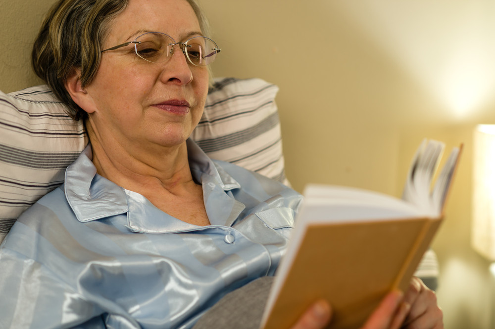 Lady reading with multifocal lenses in bed