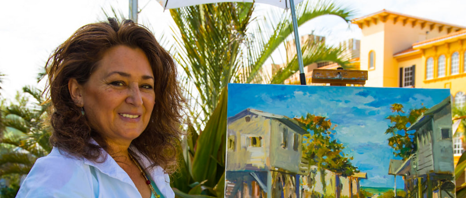 Violetta with cottage painting in front of cottages (taken by a visitor, okay to use).png