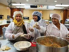 Three Somali women - Hoyo employees - in aprons, gloves, and hairnets, making sambusa pastries in a kitchen together, smiling