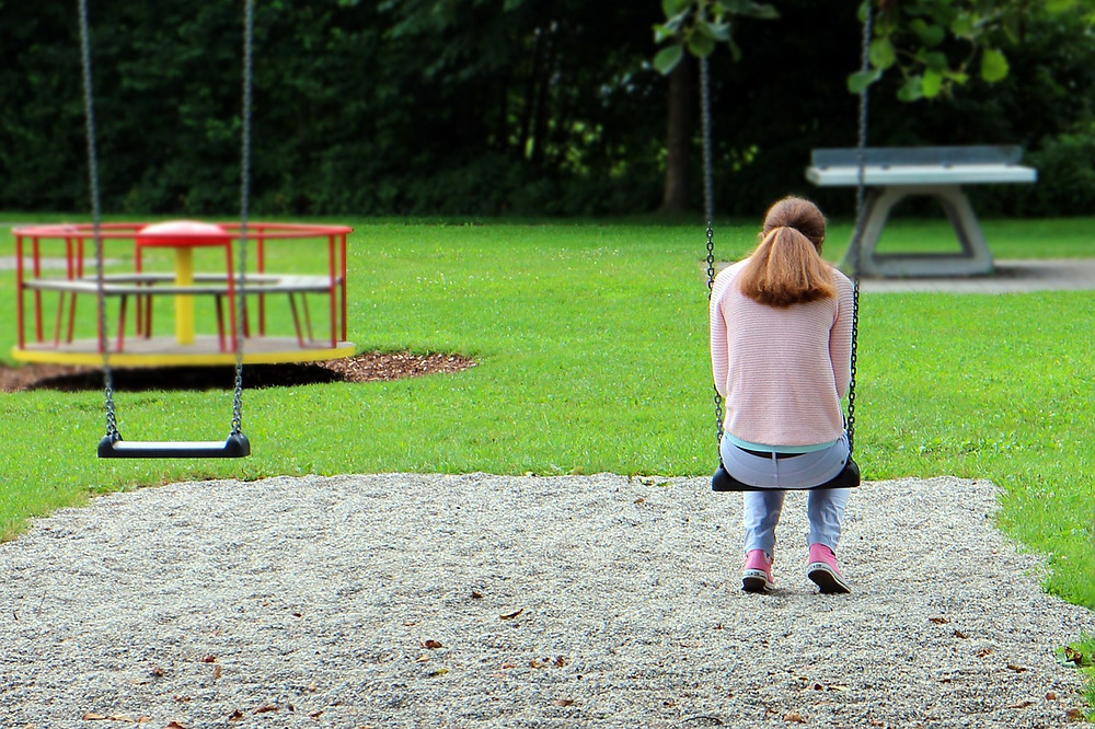 A person sits alone on a swing in the park. They look lonely and sad.