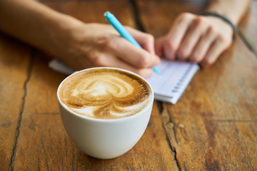 Person writing on a notepad. On the table in the foreground is a cup of coffee.