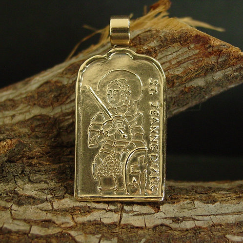 Joan of Arc pendant on branch close up