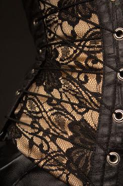 Detailaufnahme einer Corsage. Schwarze Spitze über hautfarbenem Duchesse.