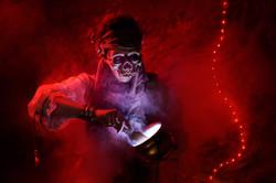Voodoopriestess preparing potions in her cave while wearing a skullmask.