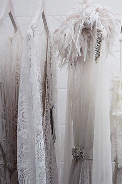 Unterschiedliche weiße Kleidungsstücke aus Spitze unnd mit Federn.