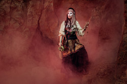 Voodoo Priestess emerging out of her cage, covered in fog.