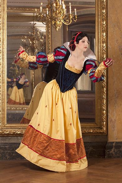 Schneewittchen steht in an die Renaissance angelehnter Kleidung vor einem goldenen Punkspiegel.