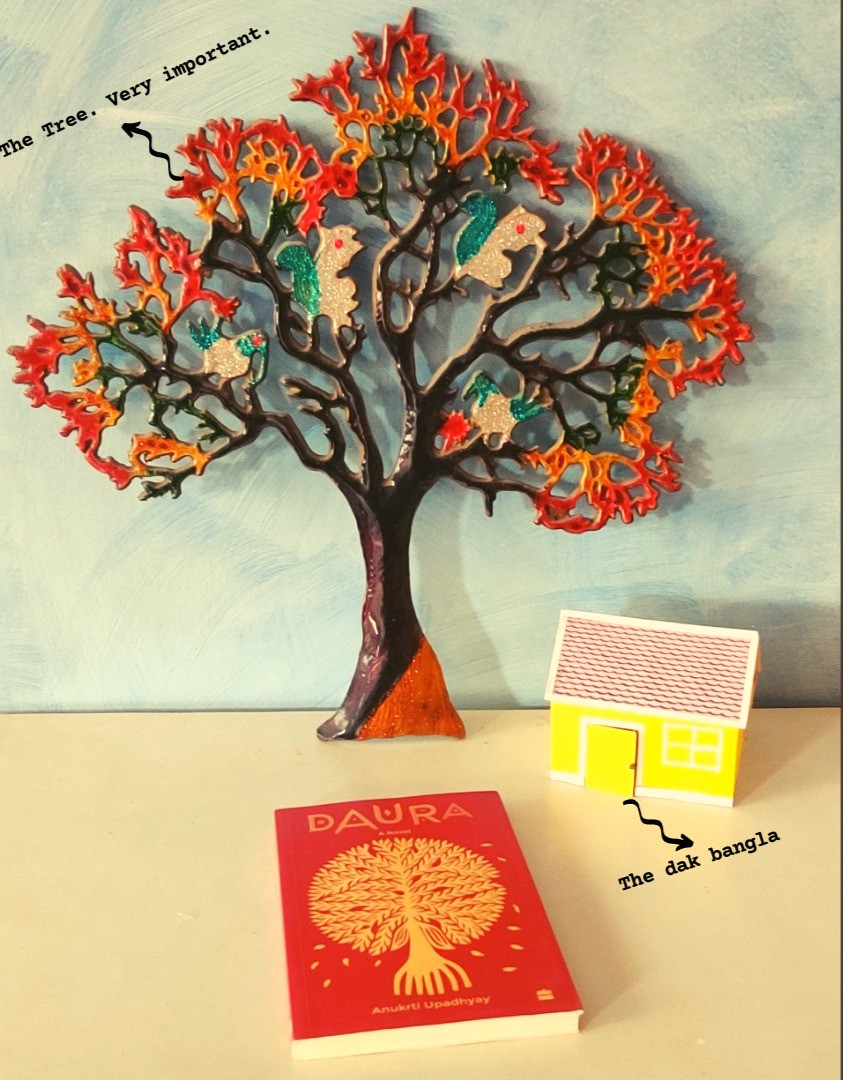 """The book, Daura, kept on a white surface. At the top is a large, colourful, shining metal tree. To the side of the tree is a much smaller yellow house, labelled """"dak bangla""""."""