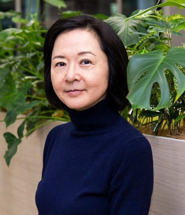 The author, Yoko Ogawa, wearing a navy blue turtleneck and posing in front of a wall with plants on top of it.