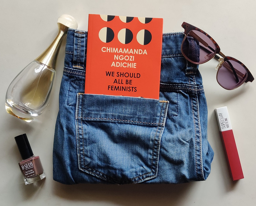 The book We Should All Be Feminists sticking out of a jeans pocket. Randomly kept are a bottle of perfume, a lipstick, a bottle of nail polish and a pair of sunglasses