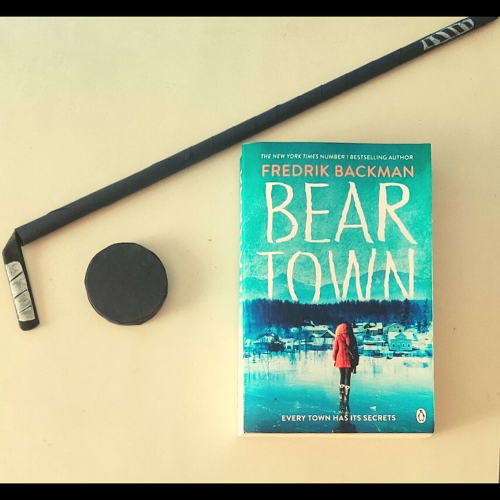The book, Beartown, kept on a white surface. An origami ice hockey stick is lying diagonally such that the bottom of the stick is at the left of the book. A black ice hockey puck is also lying to the left of the book.