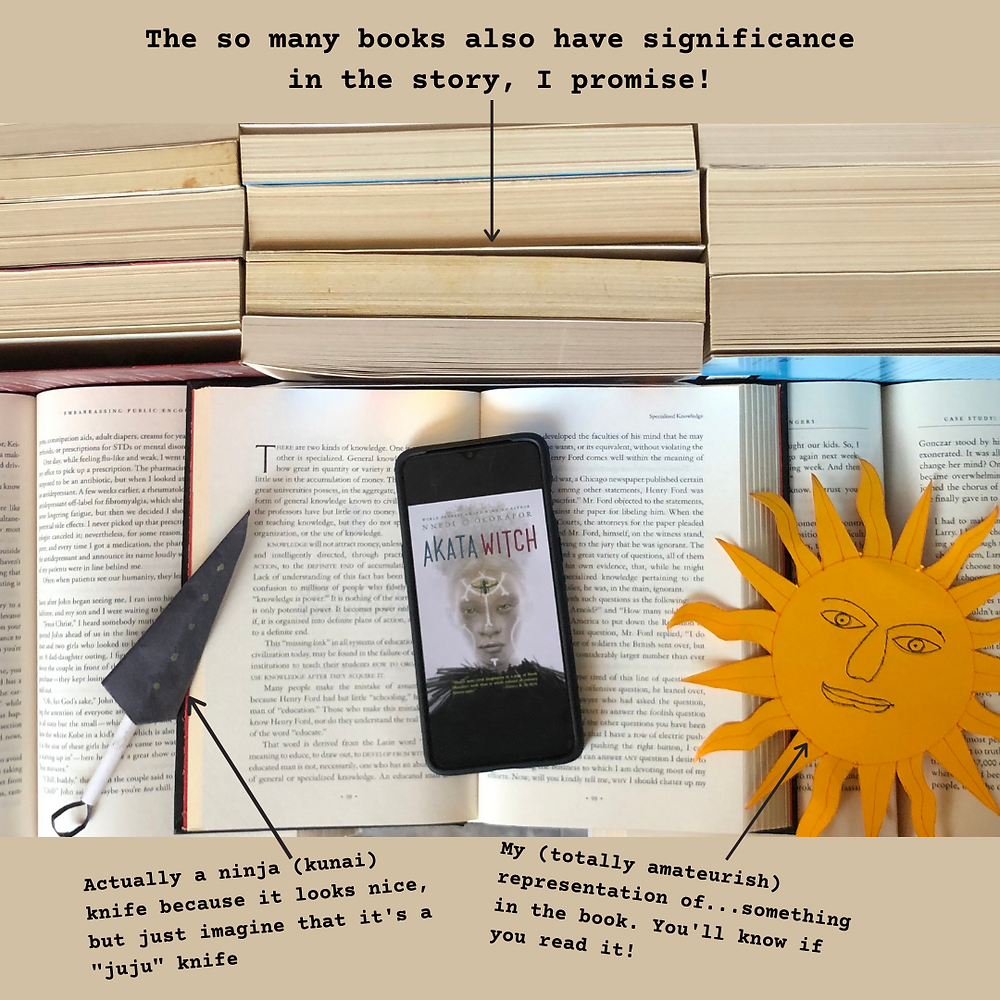 The cover page of the ebook, Akata Witch, opened on a phone. The phone sits on a book and an origami knife and a cut out of a sun are at the sides. There are books all around.
