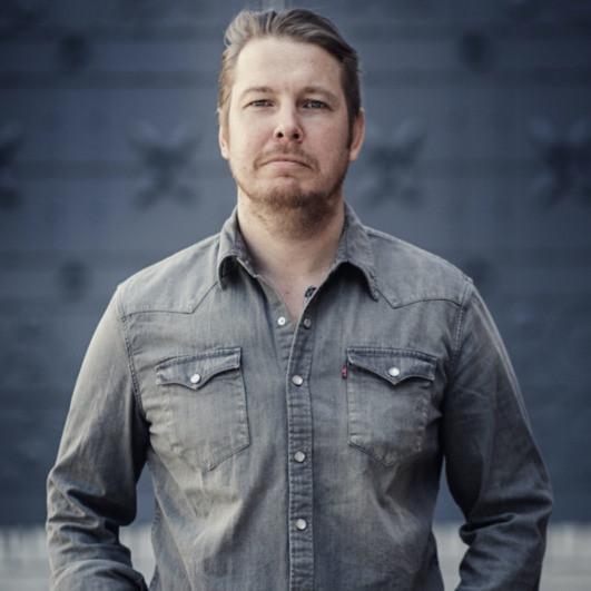 The author, Fredrik Backman, wearing a grey denim shirt, standing against a dark grey background