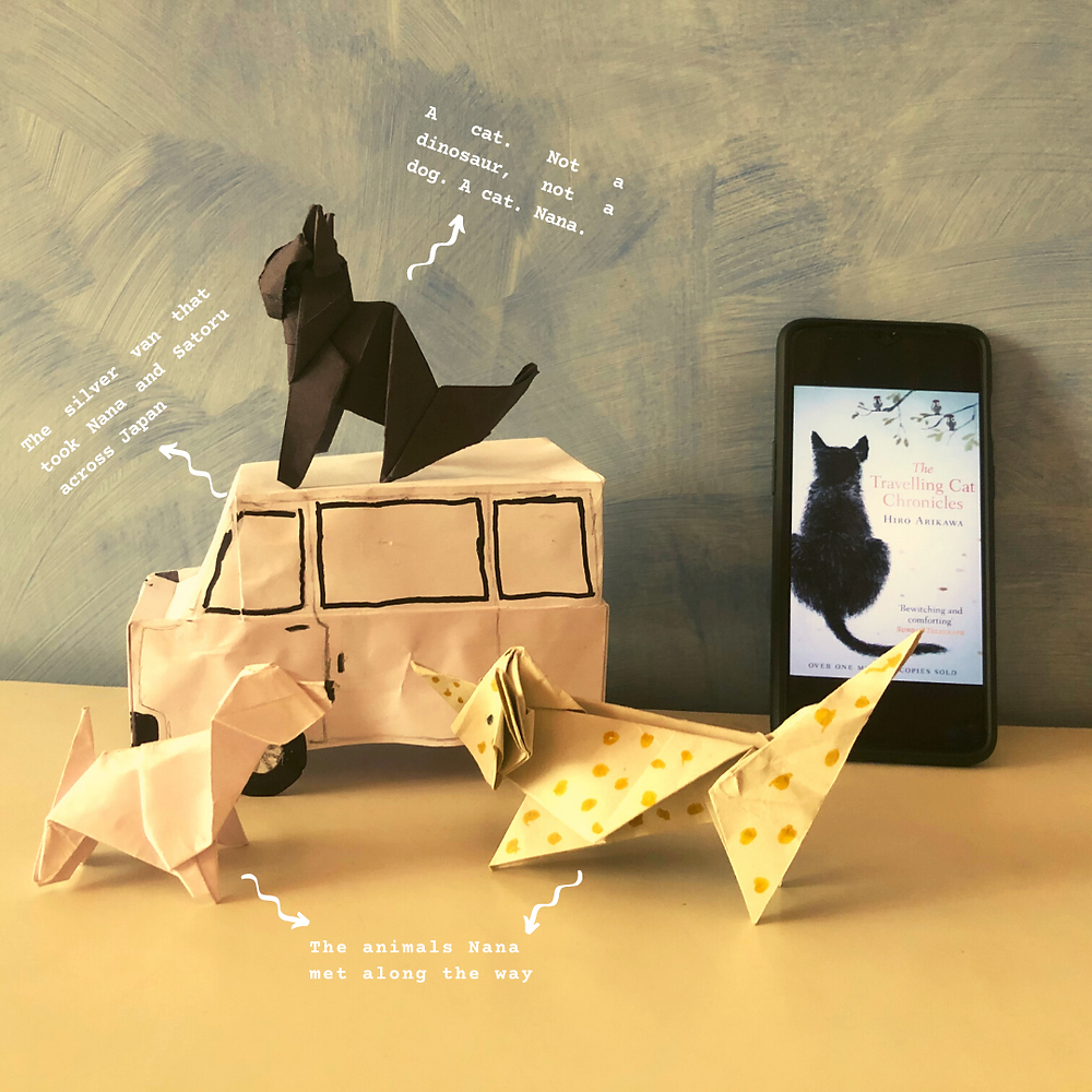 To the right of the picture is the cover page of the book, The Travelling Cat Chronicles, opened on a phone, which is leaning against a sky-blue wall. To the left of the phone is a paper van, on top of which a cat (Nana) is seated. In front of the van are a white origami dog and a spotted cat, both facing the van.