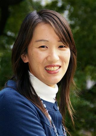 A headshot of the author, Kanae Minato, against a blurred background of trees. She's weating a white turtleneck shirt and a blue jacket on top of that.