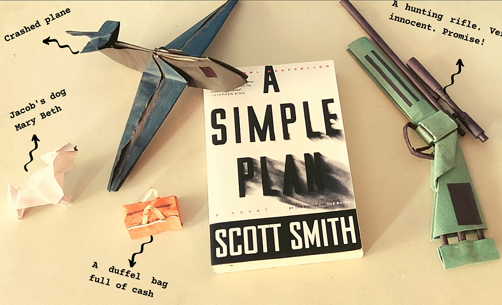 """The book, A Simple Plan, kept on a white surface. At the top left corner of the book rests an origami aircraft labelled """"crashed plane"""". Below the plane is a white origami dog labelled """"Jacob's dog Mary Beth"""", and to the side is an orange origami duffel bag labelled """"a duffel bag full on cash"""". To the right of the book is an origami hunting rifle."""