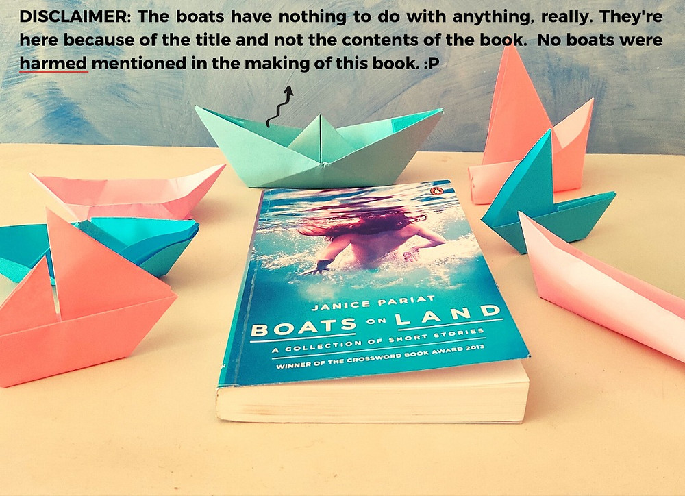 The book, Boats on Land, kept on a white surface, with paper boats all around it.