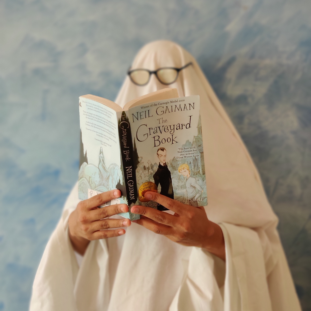 A photo of me, covered in a sheet (like a ghost), holding The Graveyard Book in my hand