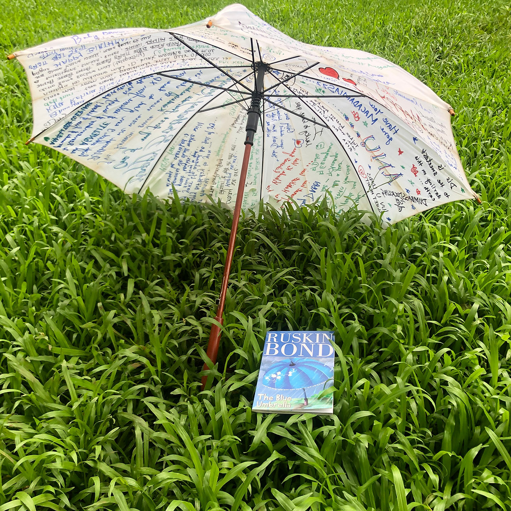 The book, Blue Umbrella, kept on grass under an open white umbrella