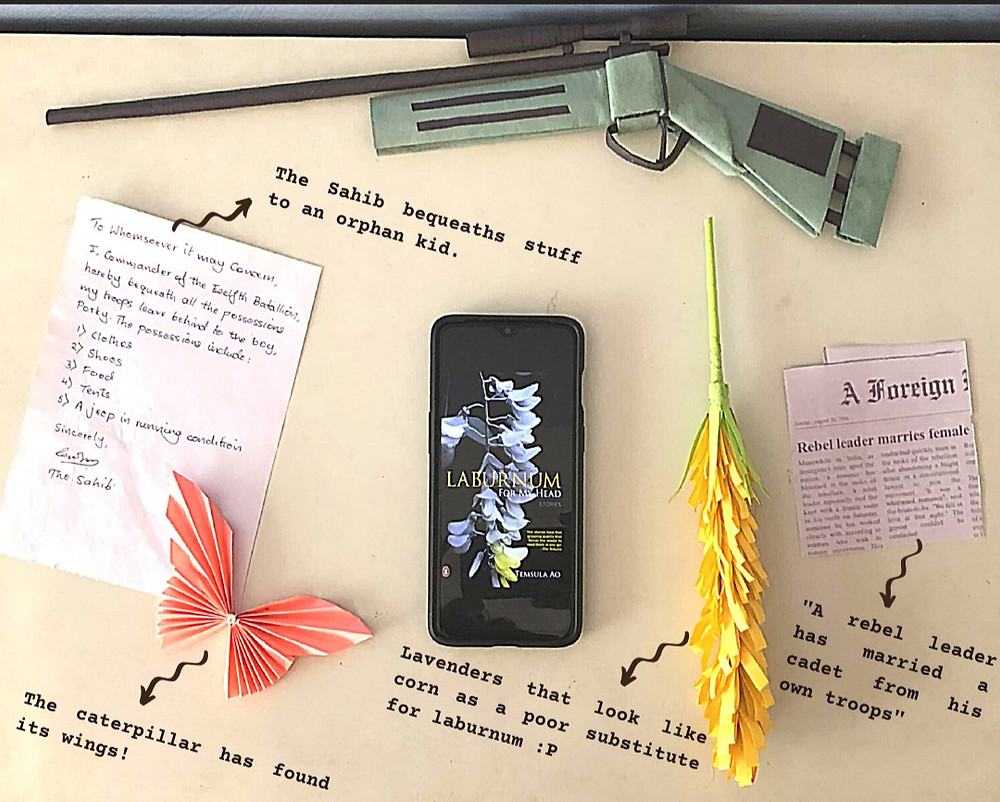 The ebook, Laburnum for My Head, kept open on a phone. Surrounding the phone is an origami gun, a paper lavender flower, a newspaper clipping, a pink paper butterfly, and a note.