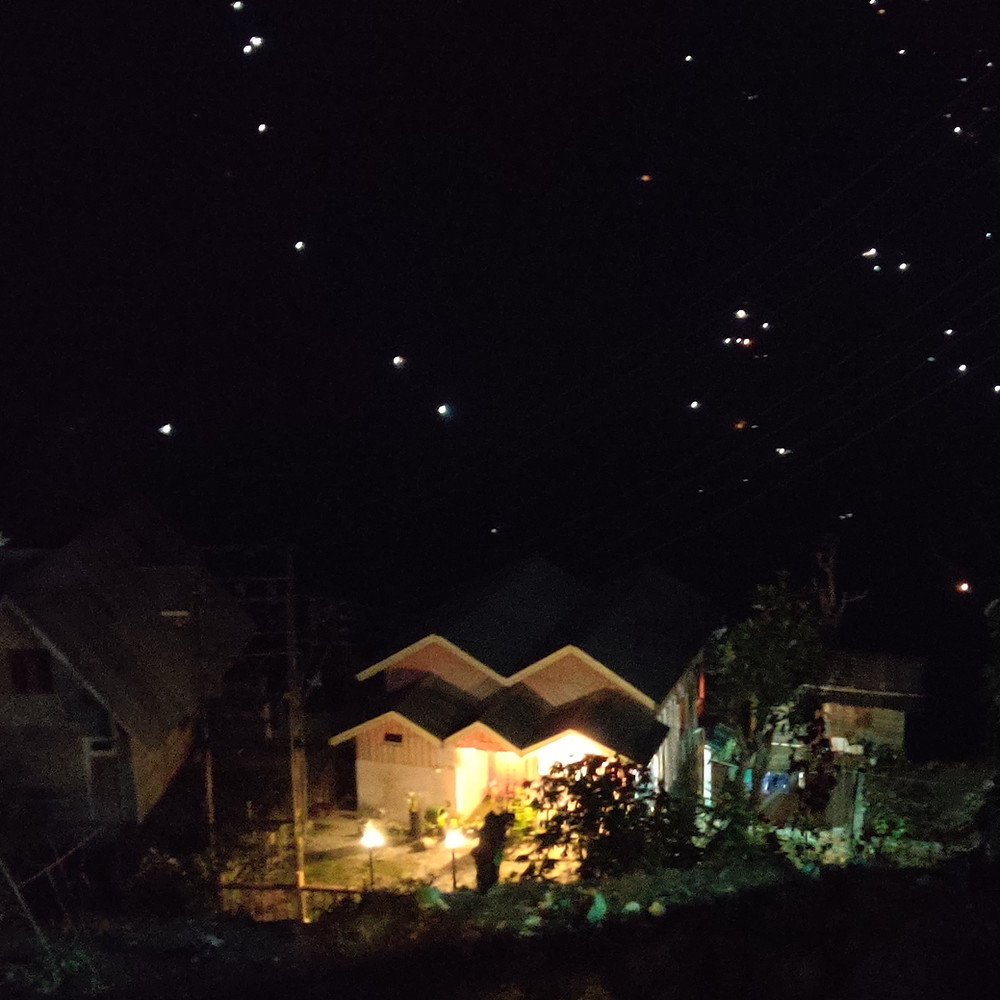 Our view at night from our homestay: A lit up home with twinkly lights in the background