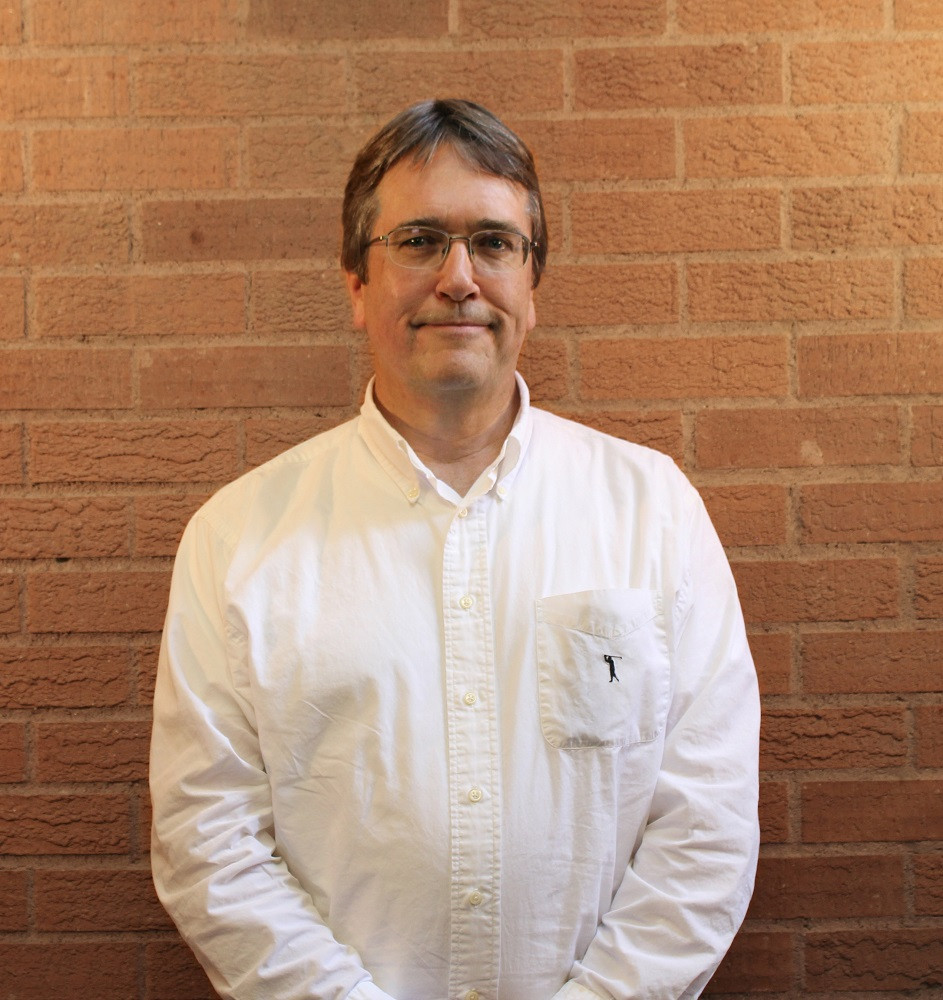 A headshot of the translator, Dr Philip Gabriel, wearing a white shirt, standing against a brick wall background
