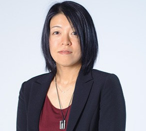 A headshot of the author, Hiro Arikawa, standing against a white background. She's wearing a maroon blouse and a black blazer.