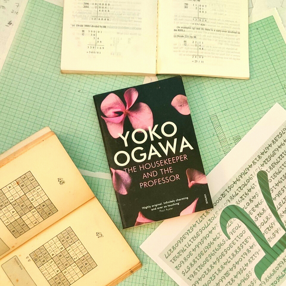 """The book, The Housekeeper and the Professor, kept on top of graph papers with equations written on them scattered around. At the top is an open book with equations on both the open pages. At the bottom left is an open Sudoku book with solved Sudoku puzzles. At the bottom right is a paper with the value of """"pi"""" written on it."""