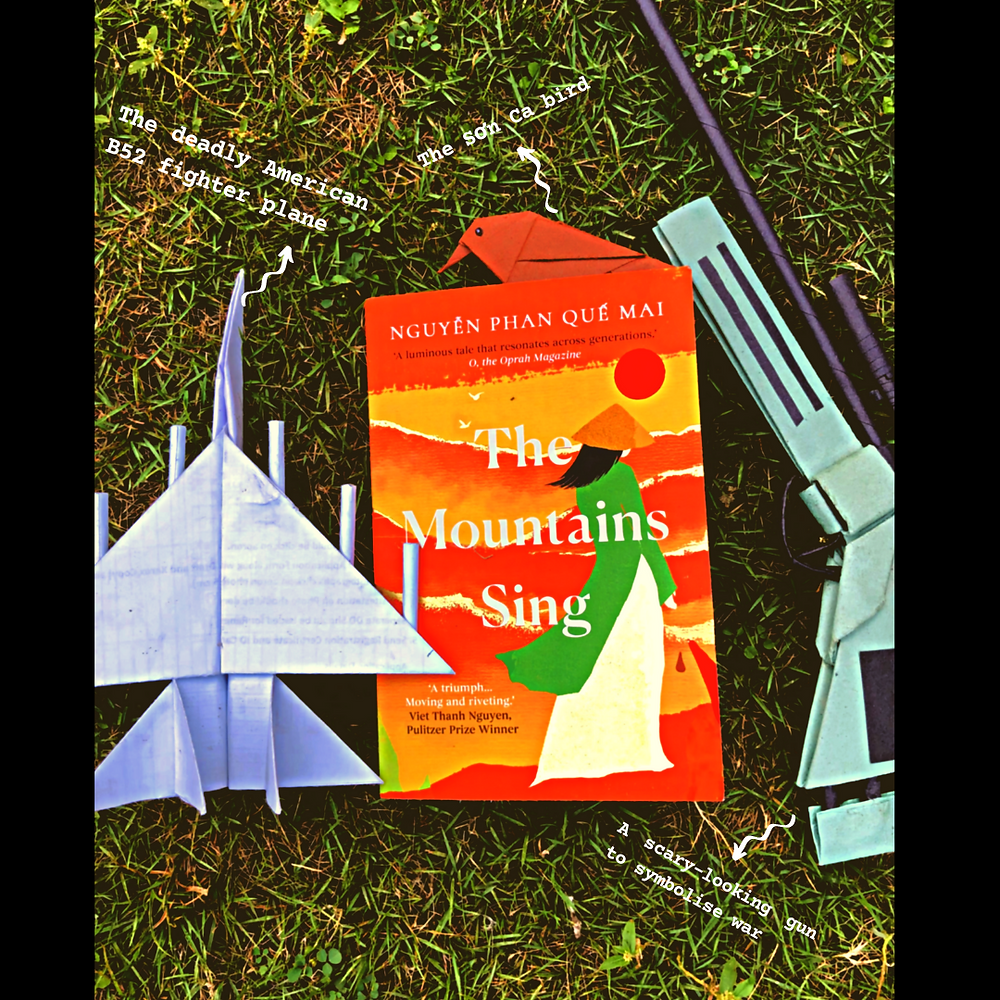 """A picture of the beautiful paperback copy of The Mountains Sing on grass. Above the book is a small brown bird (with the text: """"The son ca bird""""). To its left is a white origami fighter jet (with the text: """"The deadly American B52 fighter plane""""), and to the right is a green rifle, with the text: """"A scary-looking gun to symbolise war"""")."""