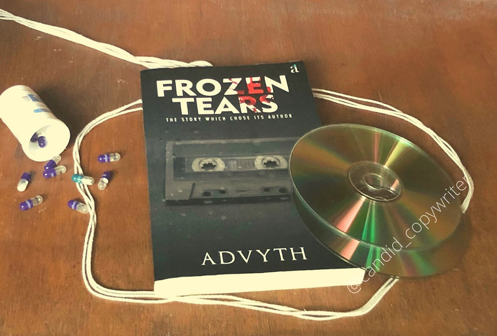 The book, Frozen Tears. Strewn across are two CDs, a bottle of pills and a rope.