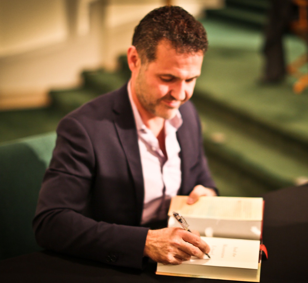A photo of Khaled Hosseini, writing inside a book.