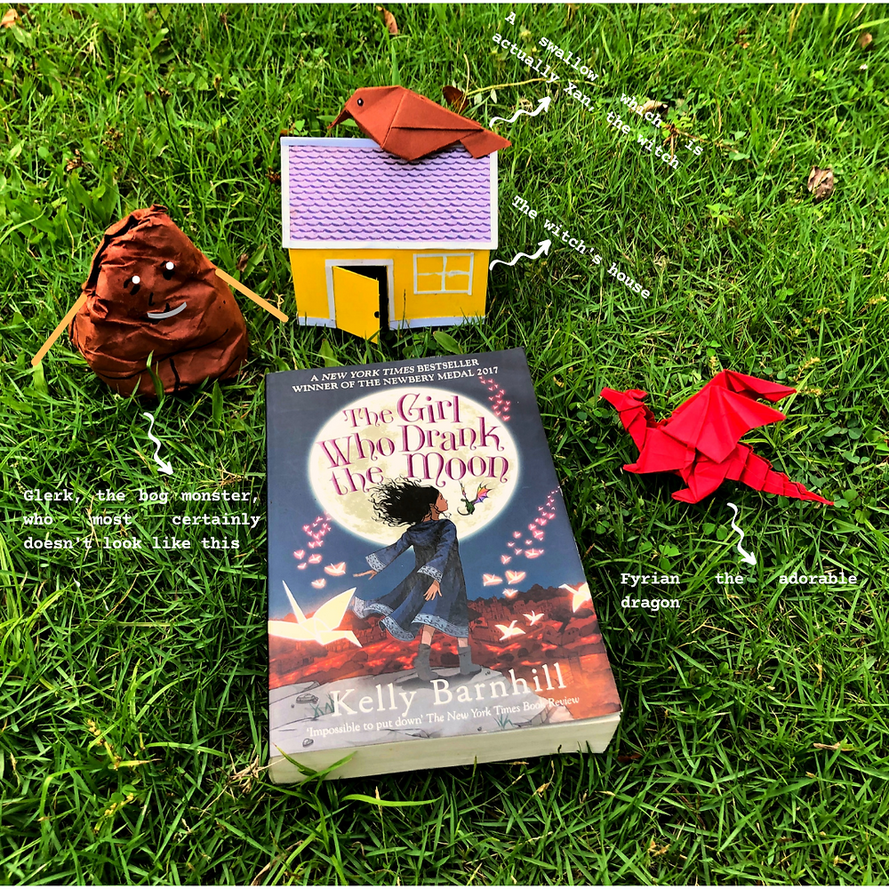 The book, The Girl Who Drank The Moon, kept flat on the grass. To the right is a red origami dragon (Fyrian). Above the book is a yellow house, labeled 'The witch's house'. A brown bird is perched on the roof of the house, labeled 'A swallow, which is actually Xan, the witch'. To the left of the house is a brown blob with eyes and a mouth and hands, labeled 'Glerk, the bog monster, who most certainly doesn't look like this'.