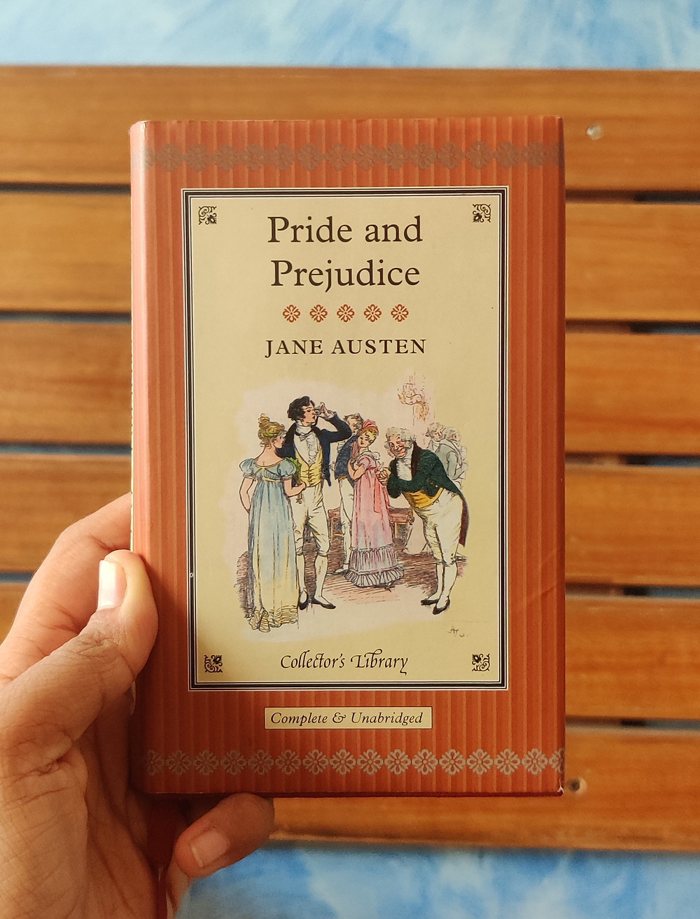 Holding a copy of the book Pride and Prejudice against a brown background