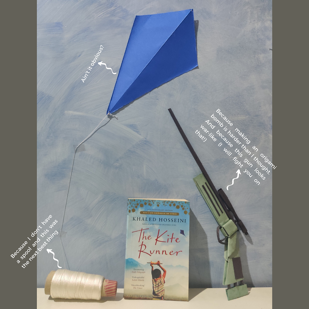 An image of the book standing against a sky-blue background. Above the book is a paper kite, and to one side is an origami gun.