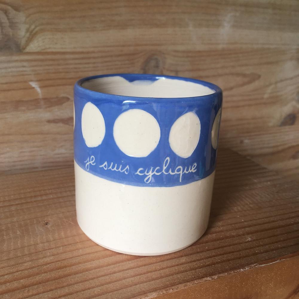 """un mug ceramique avec les phases lunaires sur fond bleu ciel et une écriture à la main """"je suis cyclique"""""""