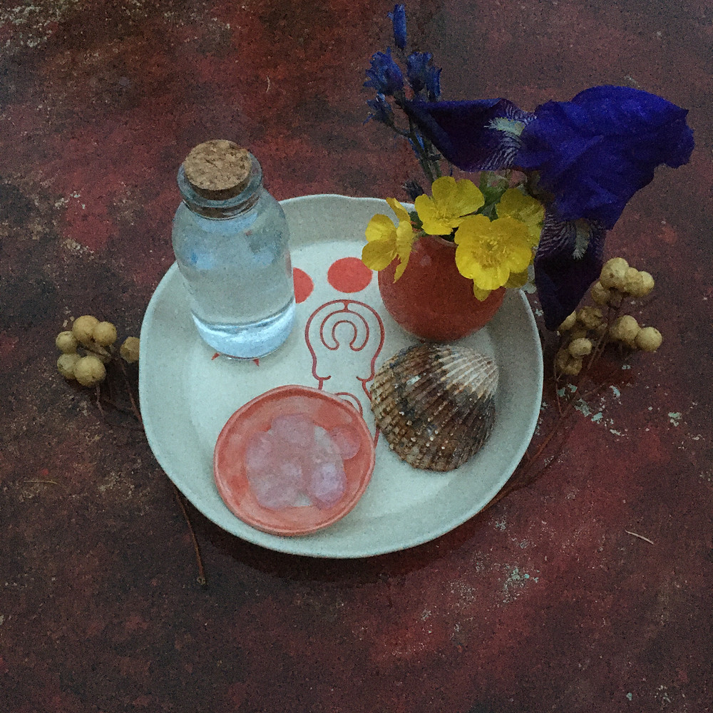 une assiette d'offrandes avec une fiole d'eau de lune un coquillage un petit vase des fleurs sauvages et des cristaux de quartz dans une coupelle