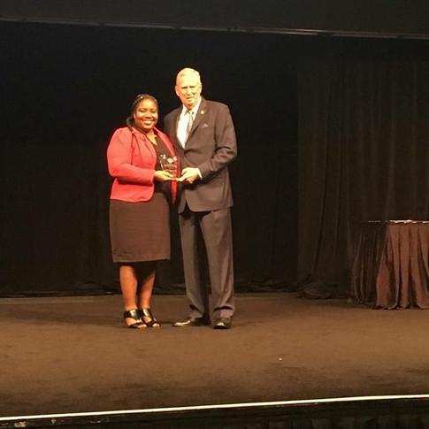President Strkey handing award to DD Godalys