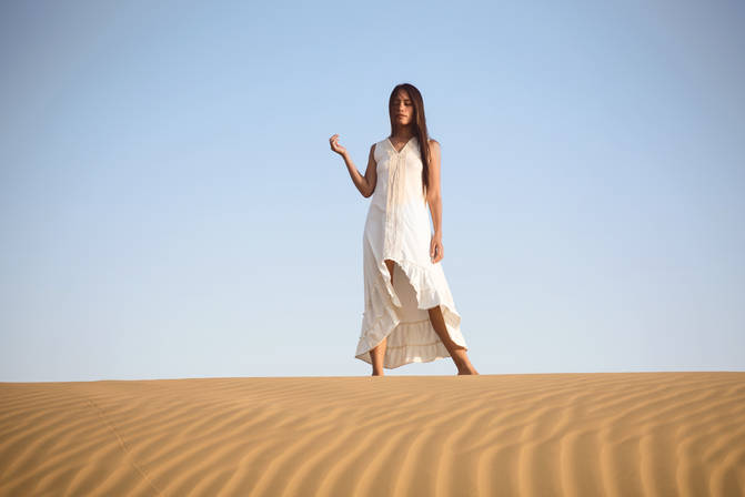 young woman in maxi dress on a sand dune