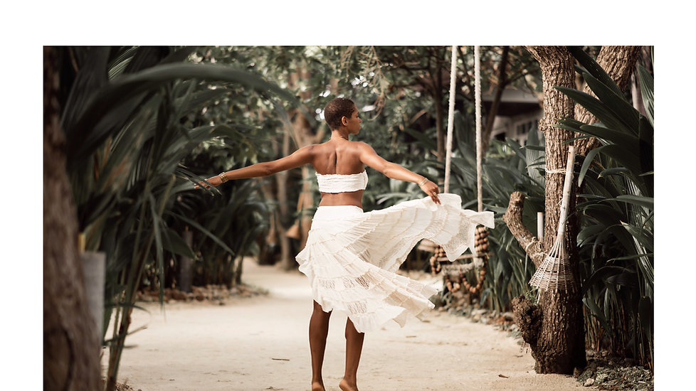 beautiful darkskin young woman wearing sustainable fashion set of skirt and top, dancing on a tropical island