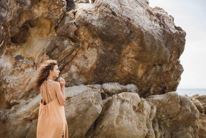 young woman in maxi dress on a rocky beach