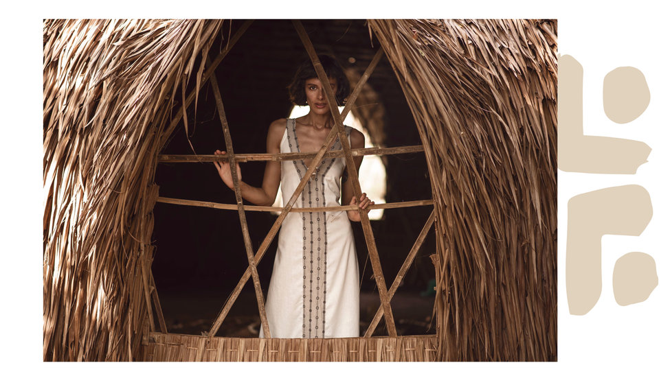 young beautiful woman wearing white maxi dress with tribal patterns made of natural materials, natural bamboo structure on a tropical island